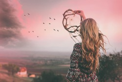 Bohemian girl with long blonde hair standing and holding dreamcatcher.Freedom