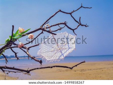 Bohemian photoshoot location with upside down white umbrella, florals ans beach backdrop