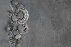 Bohemian style silver jewelry set and pebble on vintage grey background. Top view point.