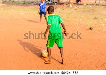 BOHICON, BENIN - JAN 11, 2017: Unidentified Beninese little boy plays football with bare feet. Soccer is very popular game among the  African kids #564264532