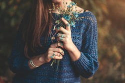 Boho chic woman in knitted blue sweater and wearing silver rings with turquoise stone with bouquet of wildflowers in hands in autumn forest outdoors in fall. Jewelry girl with boho fashion