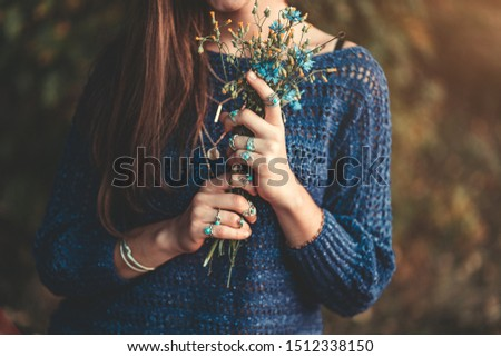 Boho chic woman in knitted blue sweater and wearing silver rings with turquoise stone with bouquet of wildflowers in hands in autumn forest outdoors in fall. Jewelry girl with boho fashion #1512338150