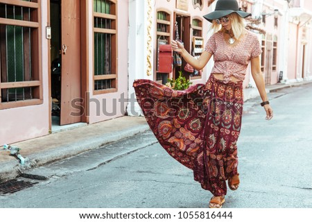 Boho girl in maxi skirt walking on the city street. Travelling in Phuket Old Town in Thailand.