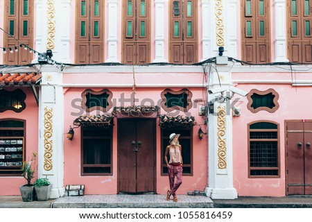 Boho girl walking on the city street. Travelling in Phuket Old Town in Thailand. #1055816459