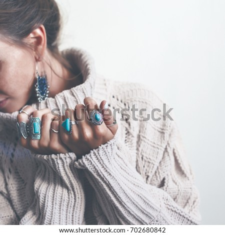 Boho jewelry on model: ethnic stone rings and earrings. Beautiful woman wearing warm woolen sweater and fashion jewellery. Minimal style and pastel tone. #702680842