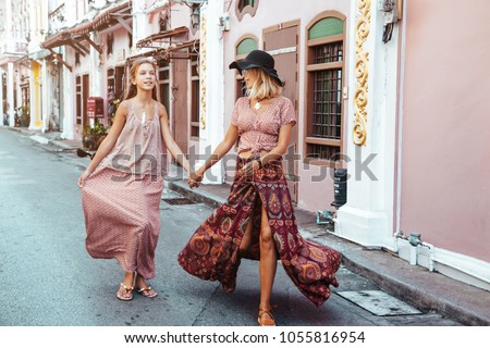 Boho mom with daughter in maxi skirt walking on the city street. Bohemian family look. Travelling in Phuket Old Town in Thailand.