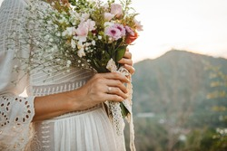 Boho style bride holding flower blossom wedding  bouquet at marriage ceremony