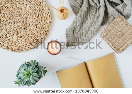 Boho style modern minimal home workspace desk with notebook, succulent, knitted plaid, candle, aroma sticks, straw wicker napkins on white background. Flat lay, top view bohemian lifestyle blog hero.