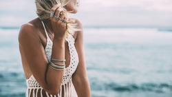 Boho styled model wearing white crochet crop top with tassels and silver jewelry on the beach