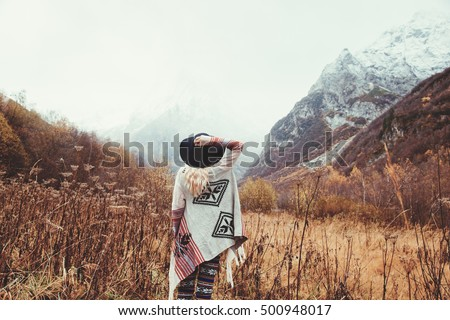 Boho woman wearing hat and poncho standing by the mountain. Cold weather, snow on hills. Winter hiking. Wanderlust. - Shutterstock ID 500948017