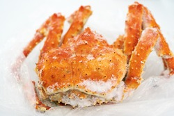 Boiled and frozen wild Red King Crab lies on plastic packaging in refrigerator. Alaskan king crab or Kamchatka crab - popular and expensive marine delicacy. Close-up view of tasty seafood.