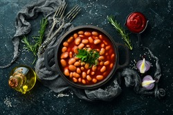 Boiled beans in tomato sauce with parsley and spices in a black metal pan. Rustic style. Top view.