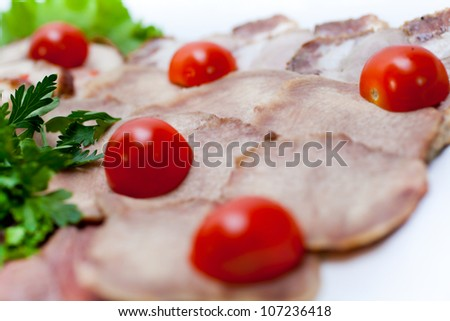 Boiled beef tongue, cut decorated with lettuce leaves, parsley and cherry tomatoes. A series of food in a restaurant close-up - stock photo