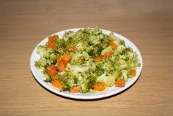 Boiled broccoli and carrots. Isolated on brown and wood background. Healthy food.