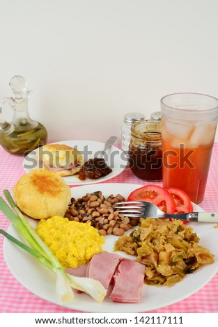 Boiled Cabbage, fried ham, black eyed peas and creamed corn soul food plate with green onions and sliced tomato.  Side plate of buttered biscuit and fig preserves with ice cold glass of sweet tea.