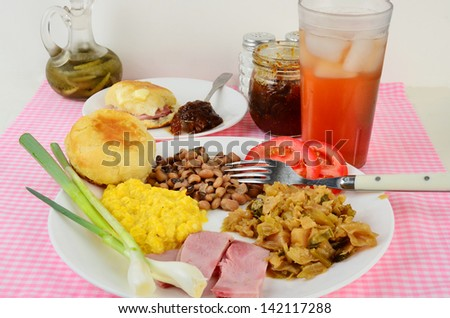 Boiled cabbage on white plate with fried ham, black-eyed peas; creamed corn and hot buttered biscuits.  Side of fig preserves, green onions, sliced tomato and glass of iced cold sweet tea.
