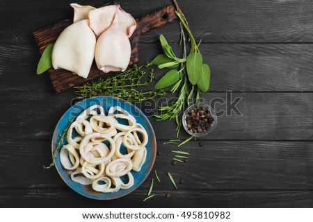 Boiled calamari squid rings on blue ceramic plate, cooked squid on cutting rings on board. Herbs for calamari squid rings thyme, sage, rosemary, black wooden background. Top view