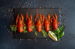 Boiled cooked crayfish crawfish ready to eat on black background. Copy space. Overhead.