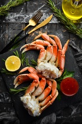 Boiled crab claws with sauce and lemon. Rustic style. Luxury Seafood Delicacies.
