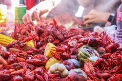 Boiled crawfish and vegetables piled on red checked tablecloth with eating tray and arm of person eating bokeh behind - shallow focus