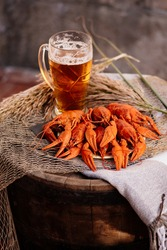 Boiled crayfish and golden beer on a wooden barrel on brick wall background