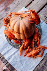 Boiled crayfish and pumpkin on white tablecloth on wooden table