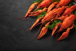 Boiled Crayfish on black plate on dark slate table top. Red crawfish with green dill and lime is popular party dish.
