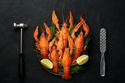 Boiled Crayfish on black plate on dark slate table top. Red crawfish with green dill and lime is popular party dish. Top view