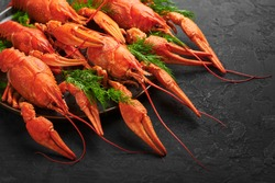 Boiled Crayfish on black plate on dark slate table top. Red crawfish with green dill and lime is popular party dish. Close up