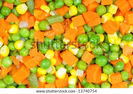 Boiled diced vegetables background with carrot, corn and peas.