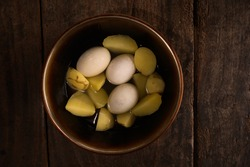 Boiled domestic duck eggs and boiled potatoes in a bowl on the water with a brown wooden background in natural light.