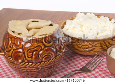 boiled dumplings in ceramic pot with curd