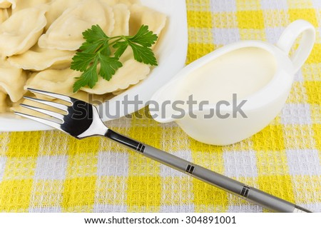 Detail · Boiled Dumplings With Parsley In Glass Plate, Sour Cream And Fork  On Yellow Plaid Tablecloth
