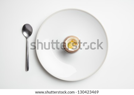 Boiled egg on plate with spoon on white table top