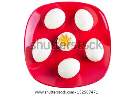Boiled eggs on red plate isolated over white