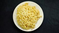 Boiled fusilli pasta on plate on black background. Boiled pasta. Macaroni casserole cook preparation.