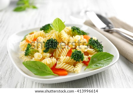 Boiled fusilli pasta with carrot, broccoli and basil on white plate Foto d'archivio ©
