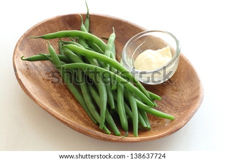 boiled green bean on wooden plate with mayonnaise