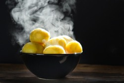 Boiled hot potatoes with steaming in a black bowl and butter served on wooden table ready to eat.