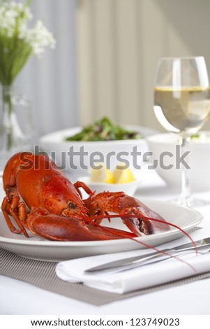 Boiled lobster and a glass of wine served on a table for dinner