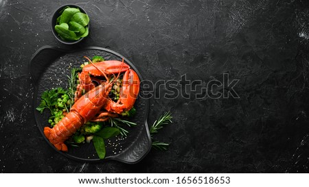 Photo of  Boiled lobster with vegetables on a black stone plate. Seafood. Top view. Free space for your text.
