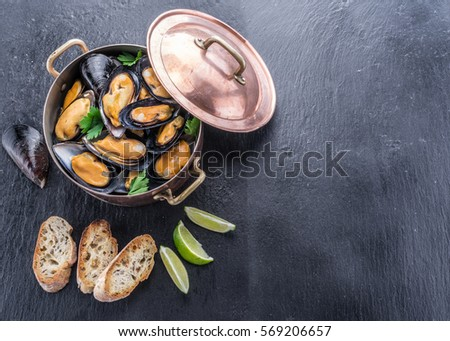 Boiled mussels in copper pan on the graphite background. Сток-фото ©