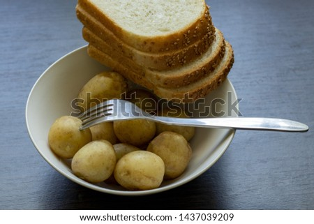 boiled new potatoes with slices of bread lay in a plate with a fork on a table in the kitchen