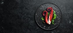 Boiled octopus tentacles on a stone plate. Seafood. Top view. Free copy space.
