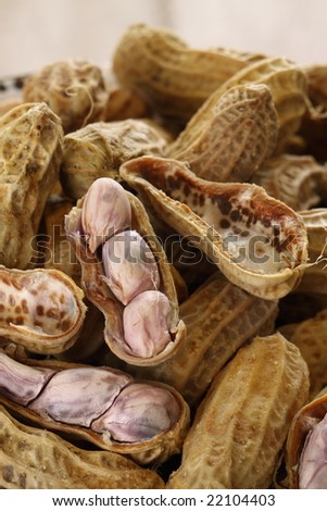 boiled peanut in a white retro bowl, some are dropped on wood ground.