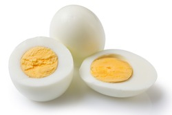 boiled peeled eggs on a white background, one whole egg two eggs are cut in half, the yolk is visible, concept