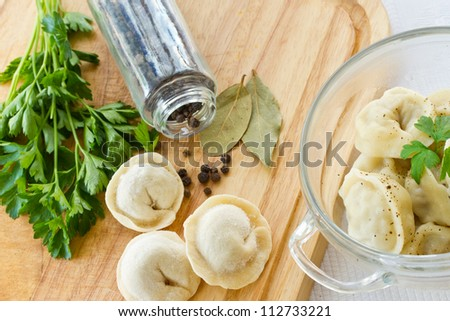 Boiled pelmeni in a bowl with spices on a light background
