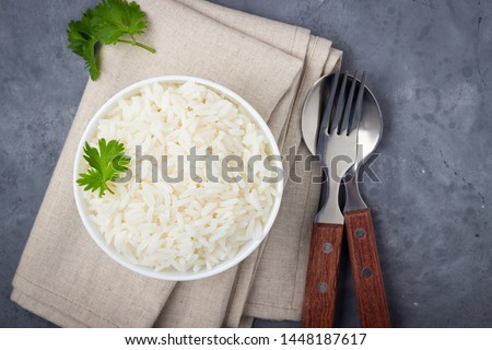 Boiled rice, cutlery and napkin on gray concrete background.