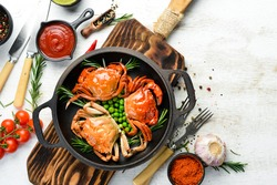 Boiled sea crabs with vegetables in a black pan. Seafood. Top view. Free space for your text.