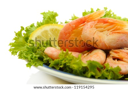 Boiled shrimps with lemon and lettuce leaves on plate, isolated on white
